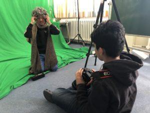 Kind filmt anderes als Wolf verkleidetes Kind vor dem Greenscreen