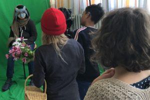 Kinder filmen als Wolf verkleidetes Kind vor dem Greenscreen
