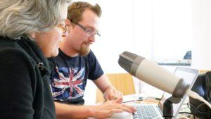 Frau und Mann vor Laptop und Mikrofon
