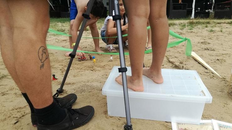 Beim Trickfilmen am Strand: Ein Mädchen steht auf einer Kiste und filmt mit dem iPad
