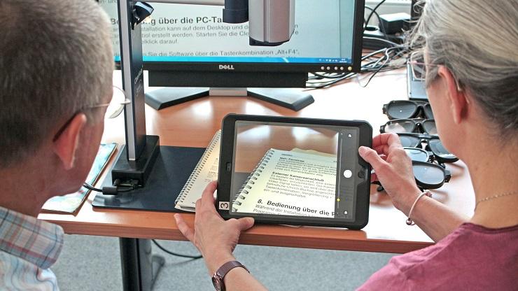 Frau benutzt iPad als Lupe. Im Hintergrund ein Lesegerät für Menschen mit Sehbehinderung