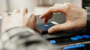 Ein iPhone wird mit dem Screenreader VoiceOver bedient. Davor liegt eine Braillezeile für blinde Menschen.