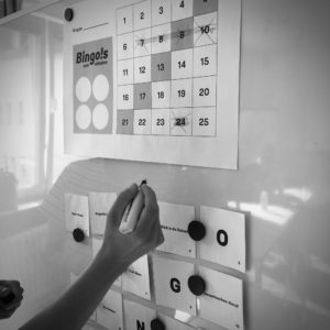 Bingo-Bogen mit durchgestrichenen Aufgaben an der Wand