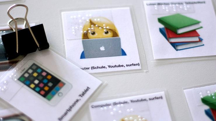 Laminierte Karten mit Abbildung verschiedener Medien mit Braille beschriftet