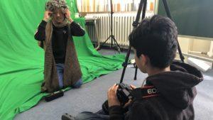 Kind im Wolf-als-Großmutter-Kostüm vor dem Greenscreen, ein anderes fotografiert