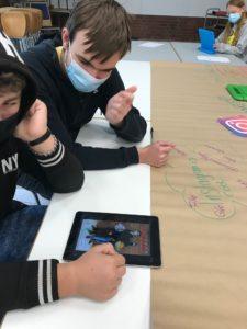 Zwei Jugendliche mit iPads und Mundschutz