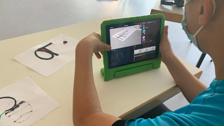 Junge mit iPad in grüner Hülle und auf Papier gezeichneten Bahnen für Mini-Roboter