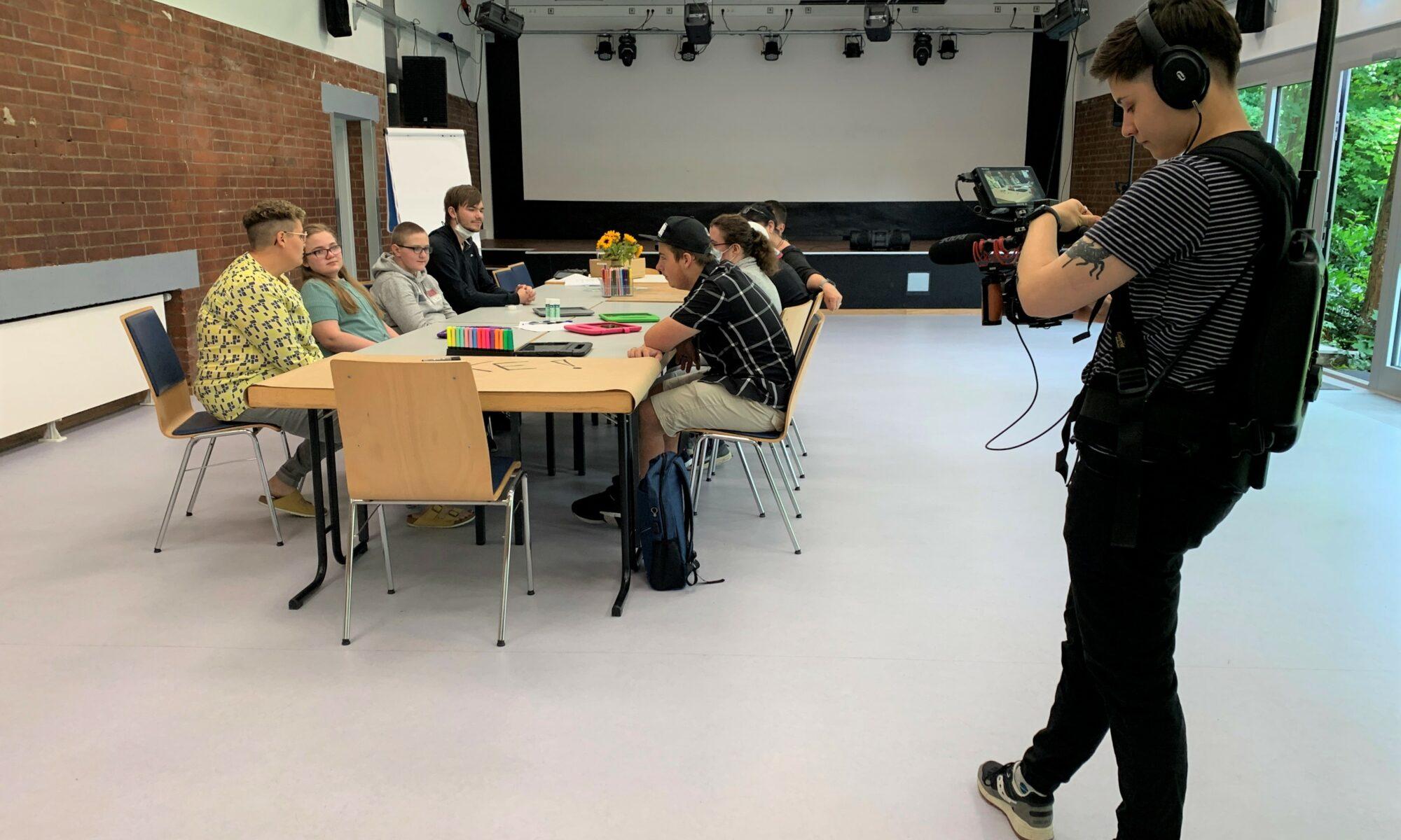 Gruppe sitzt zusammen an einem Tisch und wird gefilmt