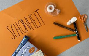 """Auf einem orangen Karton ist das Wort """"Schönheit"""" geschrieben. Daneben liegt ein Anybook Vorlesestift, mit denen Materialien vertont werden können."""